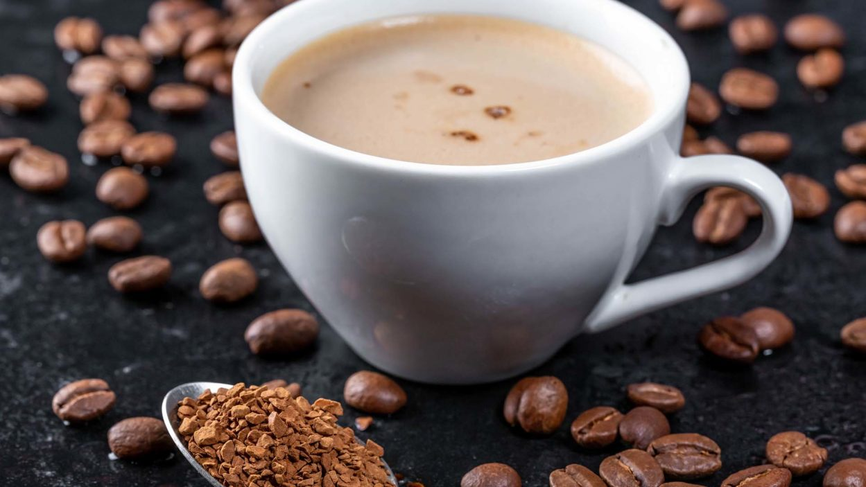 image of roasted coffee beans, ground coffee and a cup of hot coffee