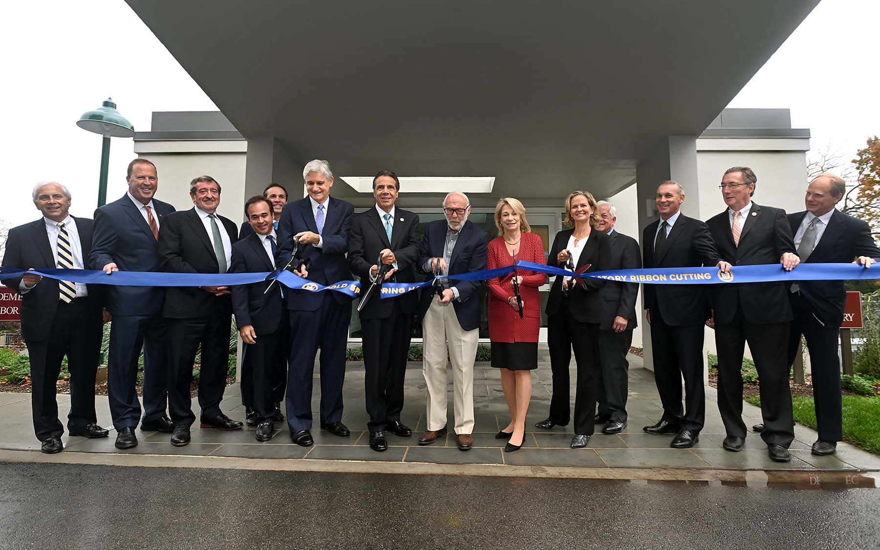 photo of Andrew Cuomo, Bruce Stillman and others cutting the ribbon in front of Demerec building