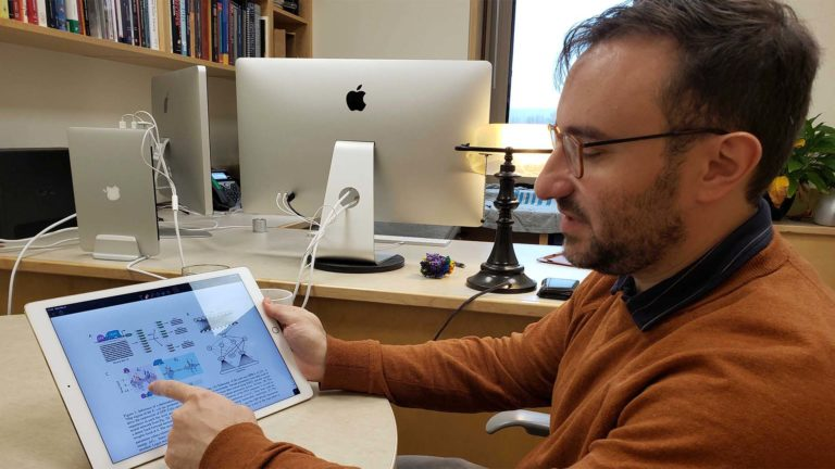 photo of Justin Kinney pointing to a model of an artificial neural network on his tablet