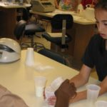 Photo of two middle school age students in a DNALC lab testing milk samples for lactase