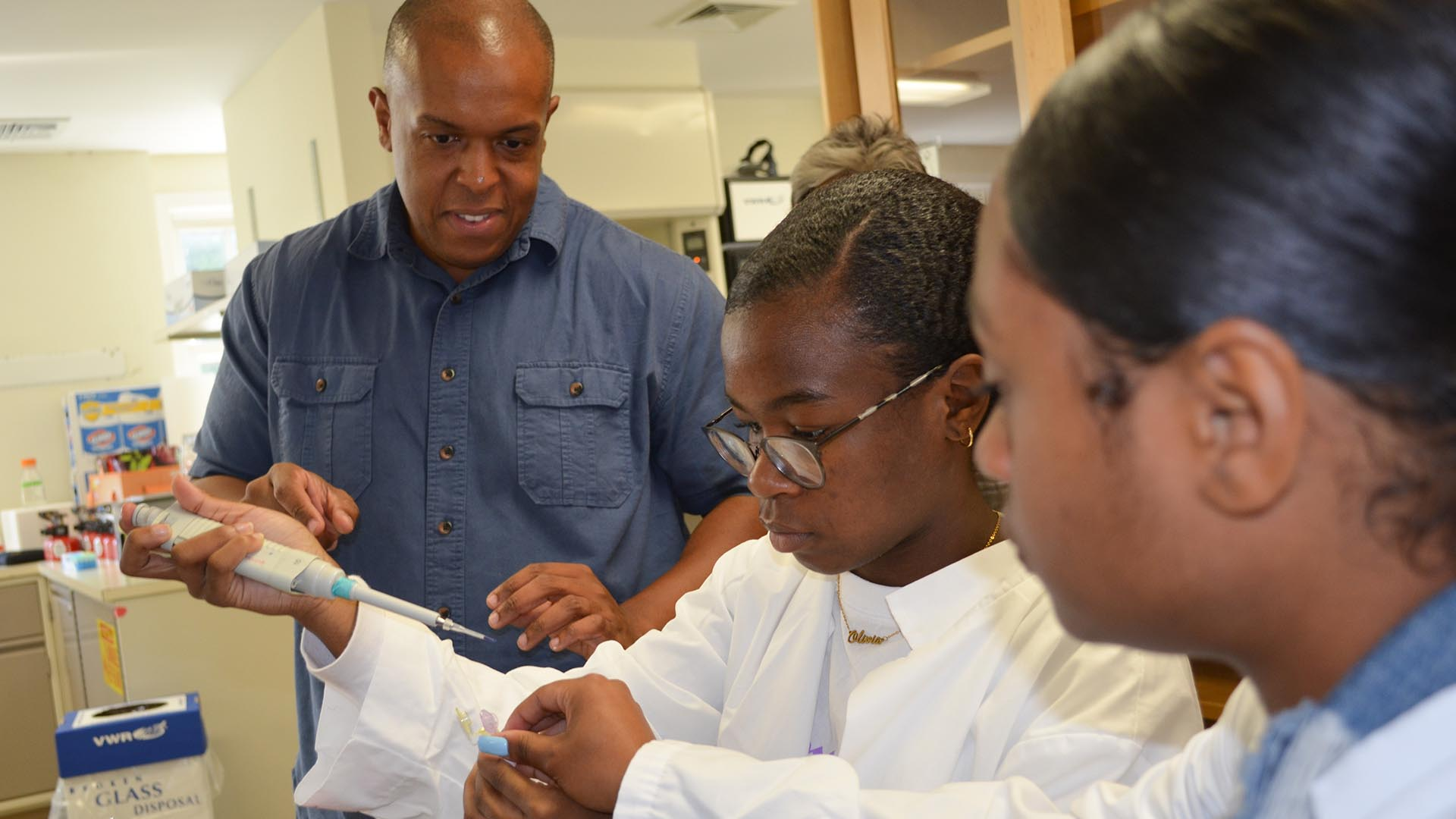 photo of Jason Williams with students pipetting