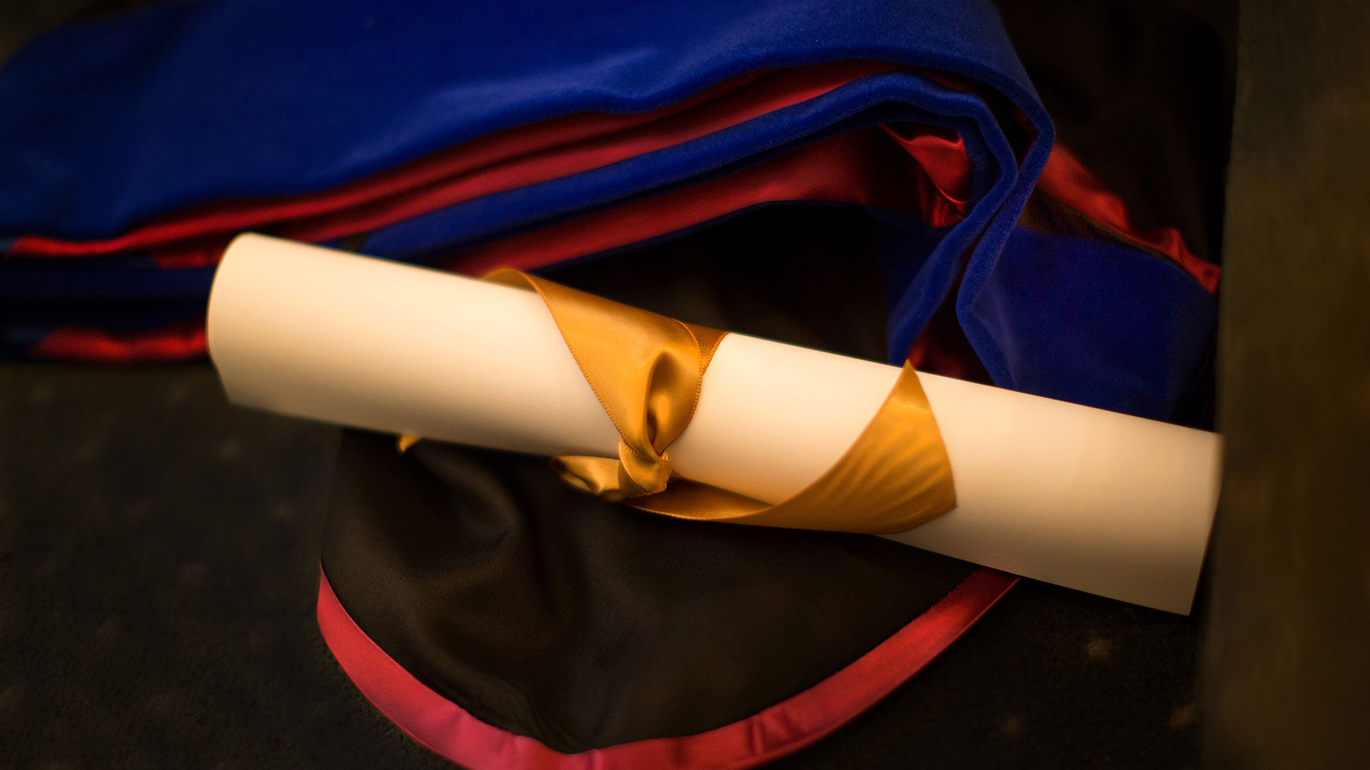 photo of graduate school diploma and gown