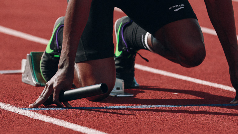photo of a runner kneeling on track