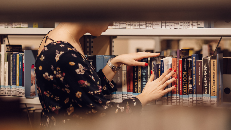 photo of librarian organizing books on library shelf
