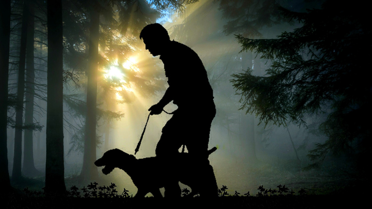 photo of man walking a dog on a leash