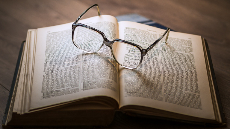 photo of an open book with reading glasses