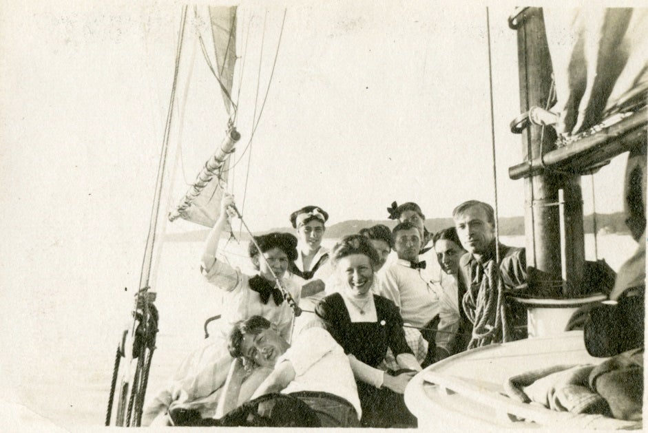 group of young men and women laughing and posing together in a sailboat