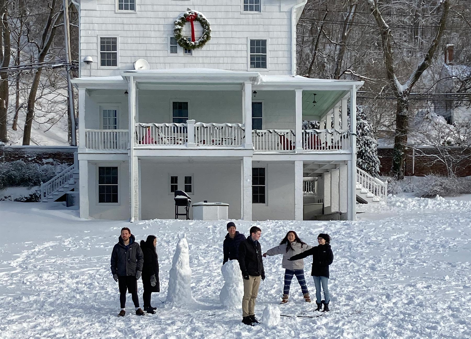 photo of SBS Grad students in front of Knight house in winter